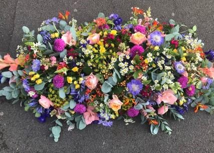 bright seasonal casket for funeral flowers